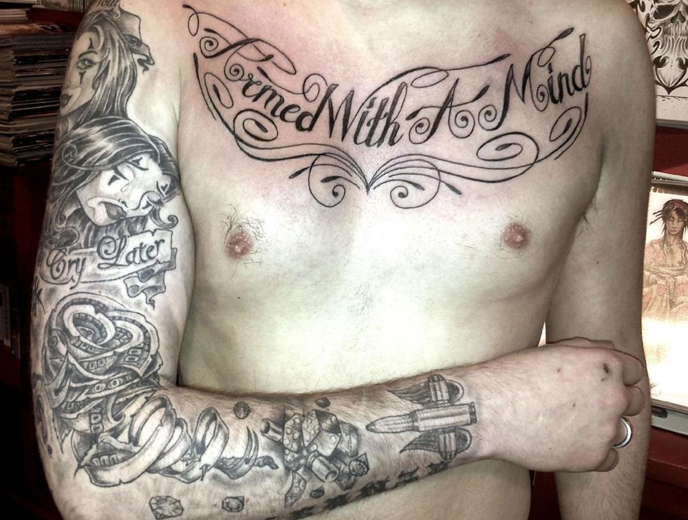 Tatouage chicanos noir et lettring poitrine et bras